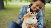 prato : Slow motion of loving African American girl pet owner stroking its dog fussing fur on its neck and looking at animal with love and care. People and nature concept.