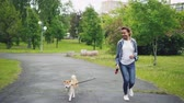 piombo : Slow motion of happy mixed race girl running in city park with beautiful small dog enjoying nature, freedom and outdoor activity. Healthy lifestyle concept.