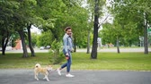 shiba inu : Slow motion of happy mixed race girl walking puppy in park and talking on mobile phone calling friends. Modern technology, loving animals and communication concept. Stock Footage
