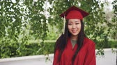 manto : Portrait of attractive Asian girl successful graduating student in gown and mortar-board standing on campus, smiling and looking at camera. Youth and education concept.