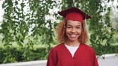 birrete : Portrait of pretty African American girl graduating student in red gown and mortarboard standing outdoors, smiling and looking at camera. Youth and education concept.