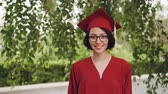 akademický : Portrait of joyful young woman graduating student in gown and mortar-board smiling and looking at camera standing under the tree on campus. Youth and education concept.