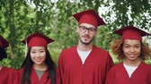 stupeň : Portrait of multinational group of graduating students in red graduation gowns and mortar-boards standing together outdoors, smiling and looking at camera.