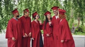 campus : Portrait of excited graduating students multiethnic group standing outdoors in red gowns and mortar-boards and talking then showing thumbs-up and looking at camera.