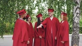 многонациональная : Joyful graduating students multiracial group are putting hands together then clapping hands celebrating graduation, friends are standing outdoors wearing gowns and mortar-boards.