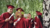 argamassa : Happy young people girl and guy are taking selfie after graduation ceremony holding diplomas wearing gowns and mortarboards. Photographs and education concept. Stock Footage