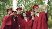 graduating : Cheerful friends graduating students are taking selfie with smartphone, young people are posing, showing hand gestures, making funny faces and laughing. Stock Footage
