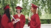 diploma : Three pretty girls graduates are talking and holding diplomas on graduation day, students are proud and excited. Conversation, education and young people concept. Stockvideo
