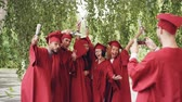 diploma : Multiethnic group of graduating students is posing for smartphone camera, waving hands with diplomas and shouting while guy is shooting them touching screen.