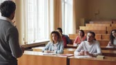 выше : Bearded man professor is reading lecture talking and gesturing while students are listening and writing sitting at tables in spacious university classroom. Стоковые видеозаписи