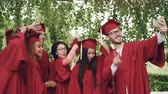 tassels : Graduating students girls and guys are taking selfie on graduation day wearing mortarboards and gowns, young man is holding smartphone, others are posing. Stock Footage
