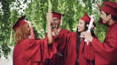 graduating : Multiracial group of young people students are doing high-five on graduation day wearing traditional clothes hats and gowns. Millennials, youth and education concept.