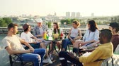 contar : Stylish young people careless friends are chatting and laughing sitting at table on rooftop having party. Beautiful city is visible in background.