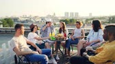 telhado : Emotional youth friends are speaking sharing news sitting on rooftop with food and drinks, multi-ethnic group is having fun in summer enjoying conversation and view.