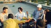limonada : Cheerful friends are chatting and drinking lemonade sitting on rooftop on warm sunny day with snacks and drinks on table. Summertime, youth and party concept.