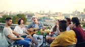 acústico : Multiracial group of young people is singing song sitting in circle on roof while young man is playing the guitar. Table with food and drinks and beautiful city is visible.