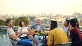 guitarrista : Students are having fun on rooftop playing the guitar, singing and dancing sitting at table on rooftop enjoying free time. Modern lifestyle and musical instruments concept. Vídeos
