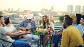acústico : Male guitarist is playing the guitar while his friends are singing, laughing and drinking beer and soft drinks at rooftop party. Modern city is visible in background.