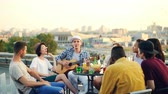 acústico : Joyful musician is playing the guitar with his friends singing and laughing sitting on rooftop at table. Entertainment, musical instruments and leisure concept.