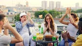 на крыше : Young woman birthday girl is making wish, blowing candle on cake and clapping hands while her friends are congratulating her and clinking bottles with drinks during rooftop party.