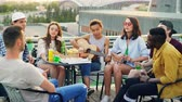 на крыше : African American girl is playing the guitar while her friends multiethnic group are singing and moving hands enjoying party on rooftop. Table with food and drinks is visible. Стоковые видеозаписи