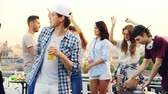 на крыше : Young people are dancing and laughing while male DJ is working with equipment at rooftop party on summer day. Entertainment, youth and music concept. Стоковые видеозаписи