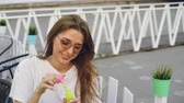 entreter : Pretty young woman wearing sunglasses is blowing soap bubbles sitting outdoors and smiling. Summertime, leisure, youth and entertainment concept.