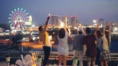 cobertura : Happy friends are burning bengal lights and dancing standing on rooftop celebrating holiday together. Entertainment, friendship, big city and joy concept. Stock Footage