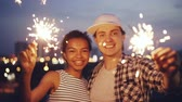 на крыше : Slow motion portrait of attractive multi-ethnic couple African American girl and Caucasian guy holding bengal lights, looking at camera and smiling standing outdoors.