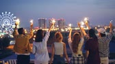 ocasião : Slow motion of happy youth friends holding sparklers and moving raised hands standing on rooftop enjoying beautiful view of big city. Friendship, fun and nightlife concept.