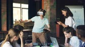 hitech : Young man wearing virtual reality glasses is having fun playing game while his colleagues are looking at him, laughing and using laptop and tablet in office.