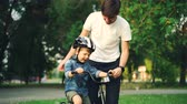 protection de la nature : Caring father is putting safety helmet on his little sons head then teaching happy boy to ride bicycle while loving mother is watching them and smiling. Vidéos Libres De Droits