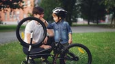 cyklus : Curious child wearing helmet is spinning bicycle wheel and pedals while his father is talking to him on lawn in park on summer day. Family, leisure and active lifestyle concept.