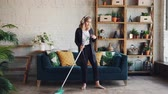 dona de casa : Beautiful young girl housewife is cleaning the house and enjoying music, she is wearing headphones, dancing and singing at home holding mop during clean-up. Vídeos