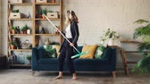 mopping : Funny young woman is singing in mop then pretending to play the guitar having fun during clean-up in modern apartment, girl is dancing barefoot on clean floor.