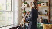 mopping : Joyful housewife is holding mop, singing in it and dancing around it enjoying cleanup in loft style apartment. Blond woman is wearing casual clothing and is barefoot.
