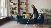 praní : Attractive girl in headphones is listening to music and dancing wih mop during domestic work, she is mopping floor at home and having fun. Women, joy and houses concept.