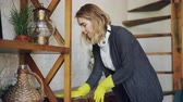 опрятный : Professional housekeeper is dusting furniture with wet cloth, woman is wearing protective gloves, casual clothing and headphones. Housework and people concept.