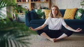 borboleta : Flexible young lady is relaxing in Badha Konasana position practising Butterfly yoga pose at home enjoying rest and relaxation. Wellbeing and people concept.