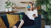 kurye : Modern young woman is resting on comfortable sofa at home with smartphone, cup of tea and headphones. Girl is listening to music, singing and enjoying drink.