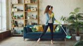 praní : Funny young lady is cleaning the house and listening to music wearing headphones dancing and singing with flat mop. Beautiful furniture and green plants are visible. Dostupné videozáznamy