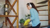 empregada : Attractive housewife is dusting the furniture and listening to the radio through wireless headphones and dancing, girl is wearing protective rubber gloves and casual clothing.