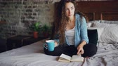 tea time : Attractive young woman with dark curly hair is reading book turning page and enjoying literature sitting on bed with cup of tea. Relaxed people, hobby and houses concept.