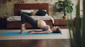 гимнастика : Pretty pregnant lady is doing sports exercises on yoga mat in bedroom wearing comfortable maternity sportswear. Healthy lifestyle and pregnancy concept.