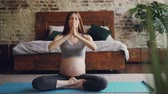 byt : Beautiful mother-to-be is practising hatha yoga in modern apartment sitting on mat and wearing maternity sportswear. Girl is sitting in lotus position and raising arms. Dostupné videozáznamy