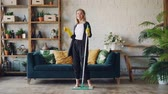 eğlenceli : Slow motion portrait of attractive blond girl listening to music with headphones, dancing with plastic flat mop and looking at camera. Housework and fun concept.