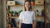 nevetés : Slow motion portrait of charming young lady looking at camera and smiling then starting to laugh standing at home with wooden shelves with plants in background.