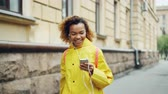 бить : Young African American woman is listening to music through earphones and dancing walking along street in modern city wearing bright clothing. Fun and gadgets concept. Стоковые видеозаписи
