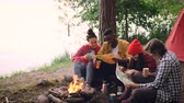 ハイカー : Cinemagraph loop - smiling guys and girls are looking at maps resting around fire in woods and holding drinks. Flame and paper is moving, beautiful nature is visible.