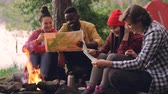 döngü : Cinemagraph loop - male and female friends tourists are sitting around fire and studying maps during hike in forest in summer. People are wearing casual clothing.